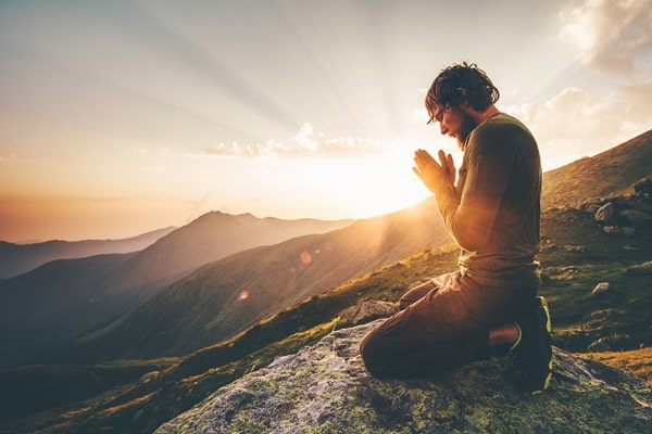 Hombre rezando puesta de sol montaña