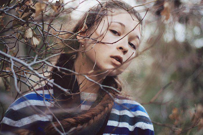foto de una muchacha cabelluda oscura con un fondo borroso del bosque.  Consejos para fotógrafos.