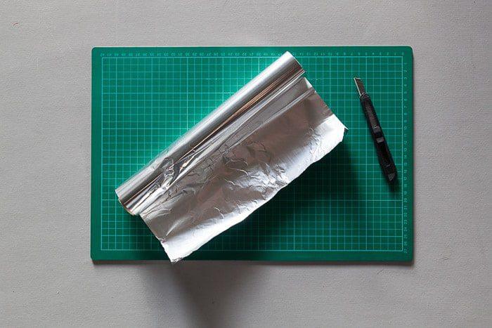 Un tiro desde arriba de una esterilla de corte, un rollo de papel de aluminio y un cuchillo Stanley: materiales para hacer una caja de luz para la fotografía