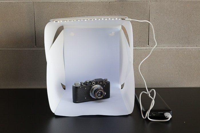 Una configuración de sesión de fotos diy que contiene una cámara en una tienda ligera diy