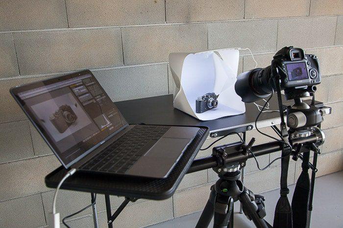 Una configuración de sesión de fotos diy que contiene una computadora portátil, una ligthbox diy, una cámara réflex digital en el trípode