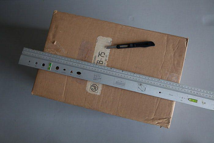 Tiro desde arriba de una caja de cartón, una regla de acero y un cuchillo: herramientas que necesita para hacer una caja de luz