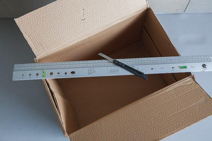 Toma desde arriba de una caja de cartón abierta y otras herramientas que necesita para hacer su propia caja de luz para fotografía