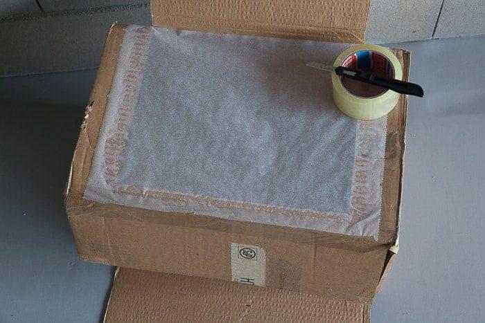 Toma desde arriba de una caja de cartón abierta y otras herramientas que necesita para hacer una fotografía de la caja de luz
