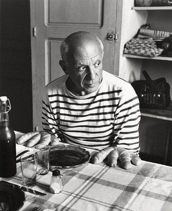 Robert Doisneau fotografía en blanco y negro de Pablo Picasso sentado en una mesa posada como si el pan fuera sus manos como ejemplos de yuxtaposición.