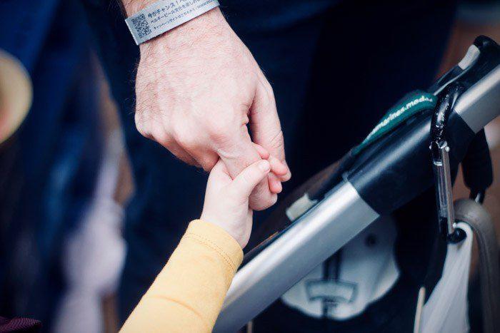 Cerrar la fotografía de una mano de un adulto sosteniendo una mano de un niño pequeño como ejemplo de ejemplos de yuxtaposición grande contra pequeño