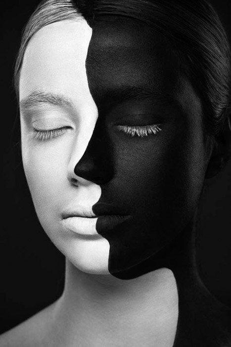 Un retrato de la cara de una mujer pintada mitad negro y mitad blanco sobre un fondo negro como ejemplo de yuxtaposición de colores.