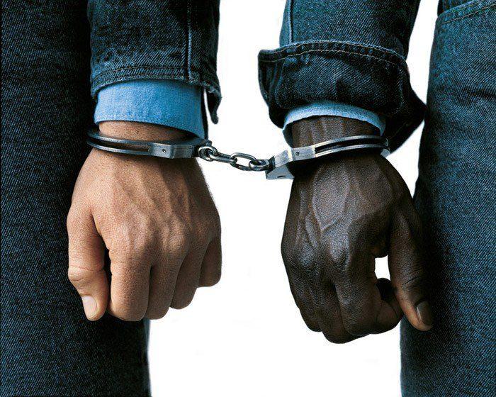 Oliviero Toscani cerca de dos manos de hombres esposadas juntas: una negra y otra blanca como símbolo de estereotipos yuxtapuestos