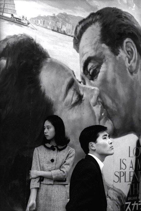 Henri Cartier-Bresson foto de un hombre y una mujer de pie yuxtapuestos contra un fondo pintado de una pareja besándose.  Fotografía de yuxtaposición de ejemplos.