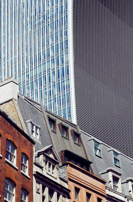 Foto de casas en estilos arquitectónicos mixtos en primer plano en yuxtaposición a un enorme rascacielos en el fondo.