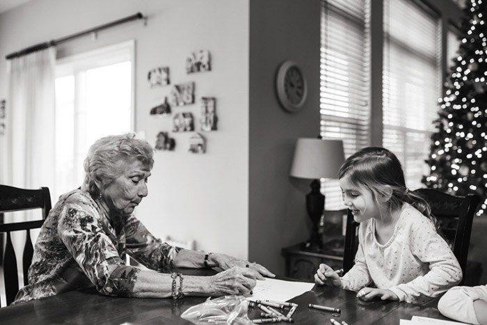Fotografía en blanco y negro de una abuela y un niño en una mesa para colorear en un libro