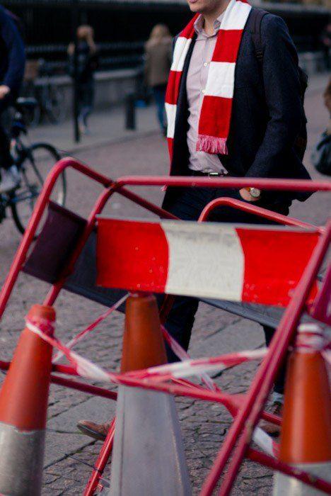 Fotografía de la calle de un hombre que lleva una bufanda que se asemeja al medio ambiente en las barreras y la cinta de la obra.  Fotografía de yuxtaposición de ejemplos.