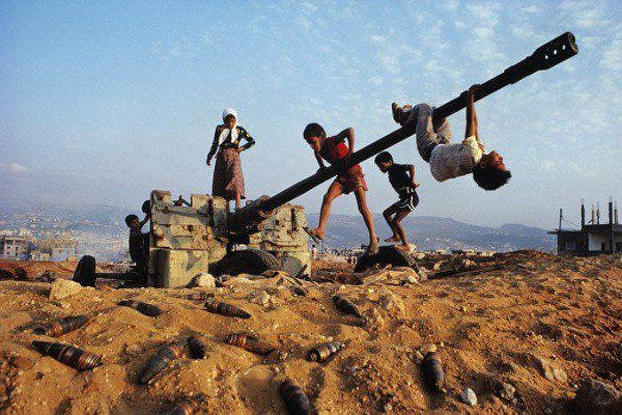 Fotografía documental de niños jugando con un arma de artillería abandonada y en desuso.