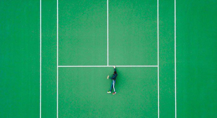 Foto de arriba de un hombre en una cancha de tenis, pero parece como si se estuviera aferrando a una repisa para la vida - ejemplos de yuxtaposición