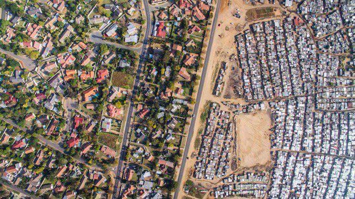 Fotografía aérea de Johnny Miller de un área densamente poblada contra un área más dispersa y más verde a la izquierda