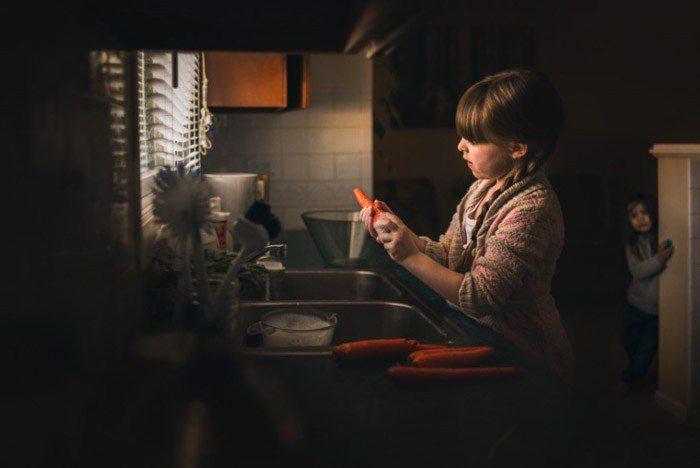 Una foto de una niña pelando zanahorias en el fregadero de la cocina: ejemplos de yuxtaposición