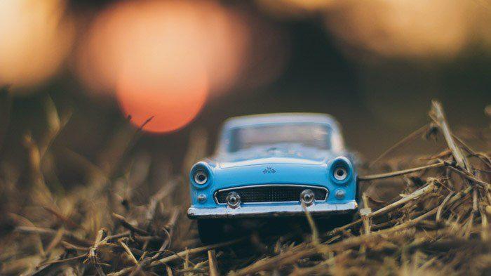 Una foto de un coche de juguete azul sobre hierba