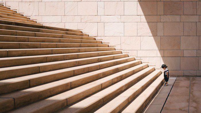 Foto de un niño pequeño de pie al final de grandes escalones de piedra: ejemplos de yuxtaposición