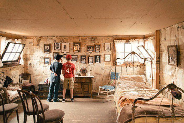 Una foto de dos niños en un dormitorio pasado de moda mirando fotos en la pared.  ejemplos de yuxtaposición