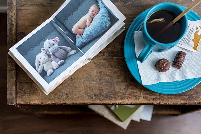 Una mesa de café plana con un libro para bebés y una taza de té: guía de precios de fotografía
