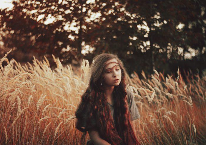 foto soñador de una muchacha cabelluda oscura en un campo de maíz con un fondo borroso del bosque.  Consejos para fotógrafos de retratos.