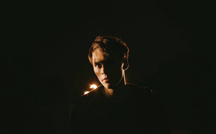 foto nocturno de un hombre con un lado de su rostro iluminado, fondo oscuro.  Consejos para fotógrafos de retratos.