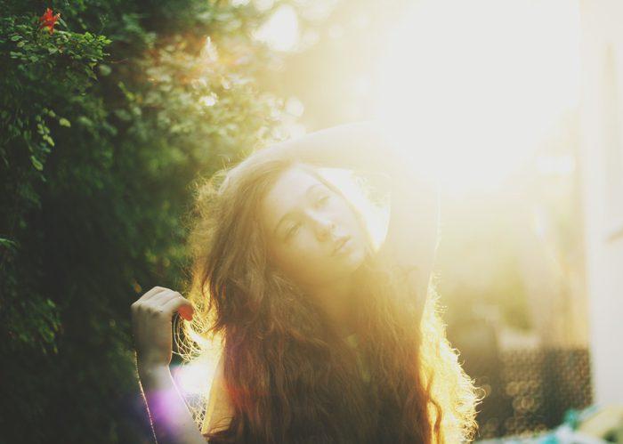 La luz soñadora llenó la foto de una muchacha cabelluda oscura con un fondo borroso del bosque.
