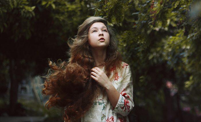 foto de una muchacha cabelluda oscura con un fondo borroso del bosque.