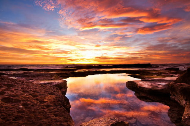 Las nubes rosadas, anaranjadas y doradas se reflejan en la superficie de esta charca de mareas, hacen que la foto sea doblemente colorida.