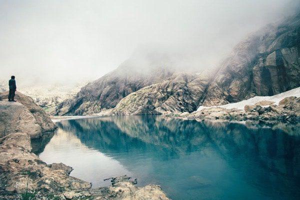 Hombre acantilado lago niebla