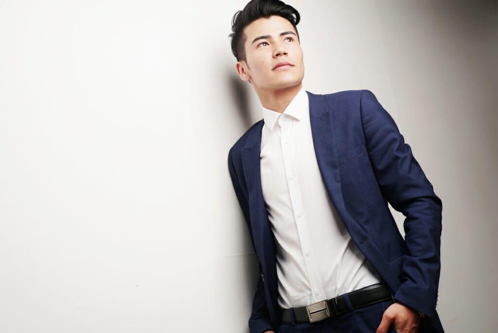 Posiciones masculinas: Un modelo masculino está posando mientras se apoya en una pared.  Disparo desde un ángulo bajo para que parezca más alto