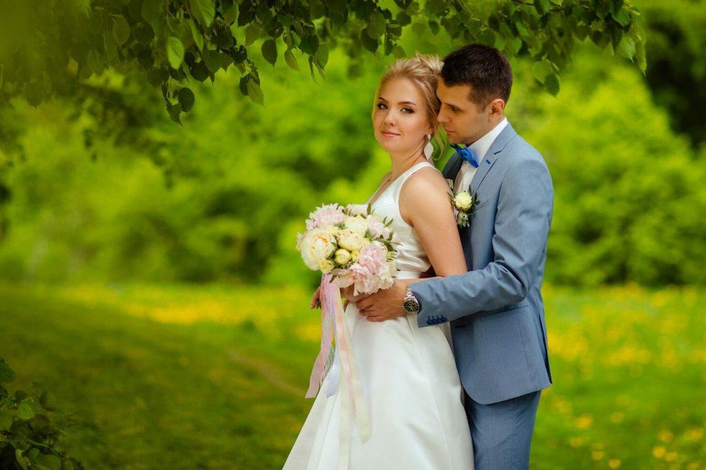 Poses de bodas: Un novio mira a su novia debajo de un árbol, demostrando una de las posturas clásicas de la boda en primer plano