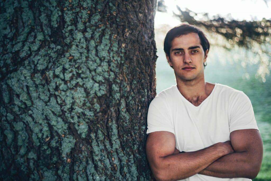 Una foto recortada de un hombre posando con una camiseta blanca inclinada a un lado contra un árbol