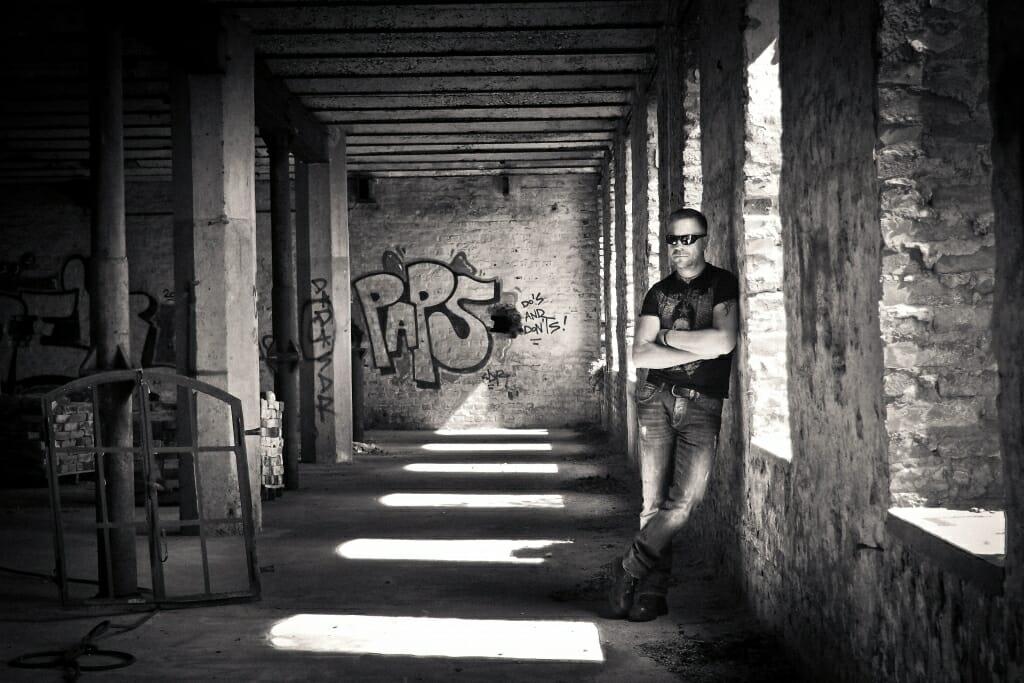 Un hombre posando de pie junto a una ventana en un almacén abandonado.