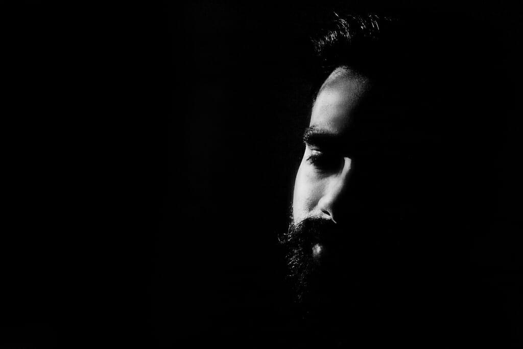 Posiciones masculinas: Una pose masculina en blanco y negro donde la cabeza está inclinada hacia un lado.  Solo parte de la cara está bien iluminada