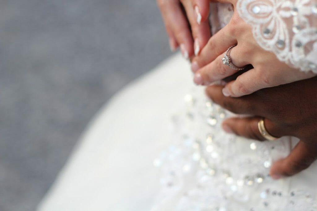 Poses de bodas: Un primer plano de las manos y los anillos de boda de los novios