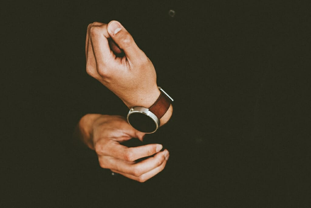 Una pose masculina donde solo las manos y el reloj del hombre son visibles.