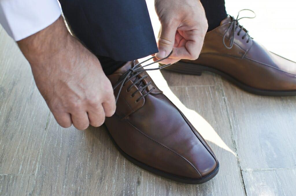 Una foto de un hombre atando sus zapatos.  Foto tomada con mucho zoom para mostrar los detalles de espectáculos, manos y cordones de los zapatos.